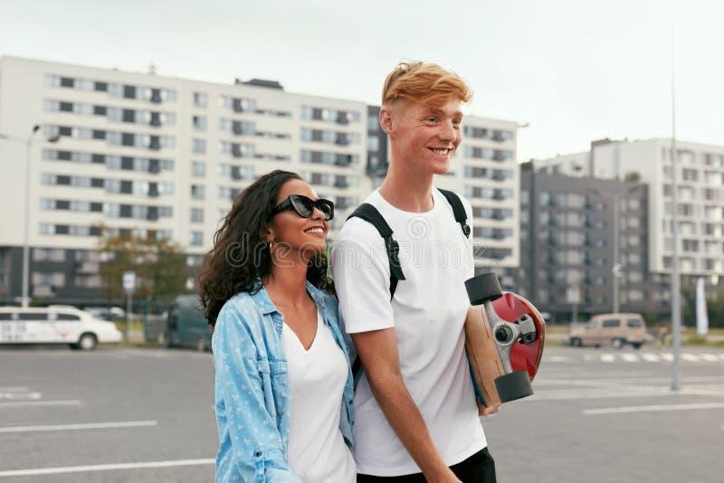 Barnet kopplar ihop med skateboarden som har gyckel på stadsgatan arkivfoto