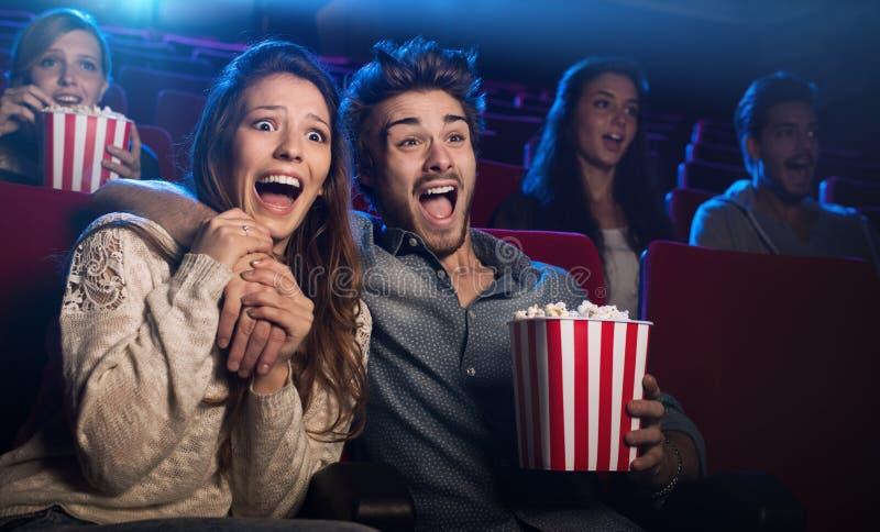 Barnet kopplar ihop på bion som håller ögonen på en fasafilm royaltyfria bilder