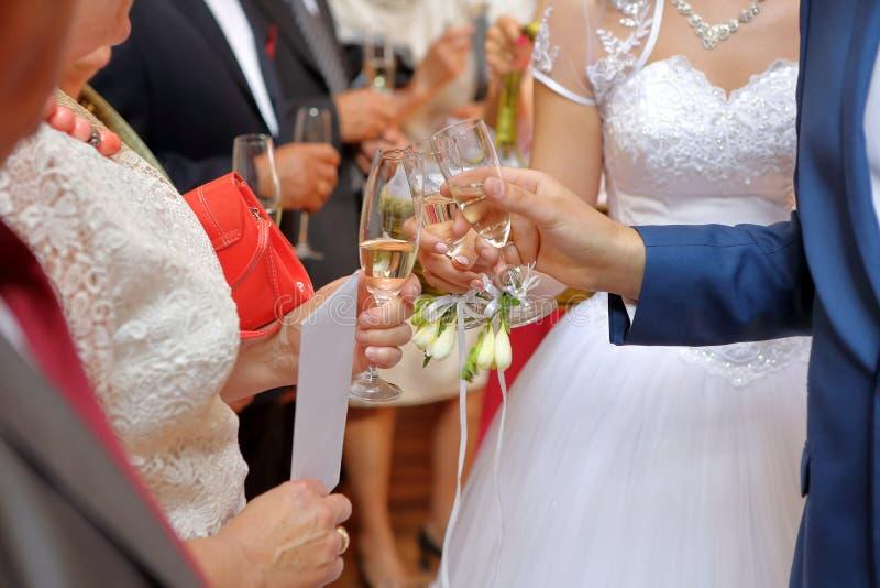 Barnet kopplar ihop på ett bröllopmottagande med champagneexponeringsglas arkivfoton