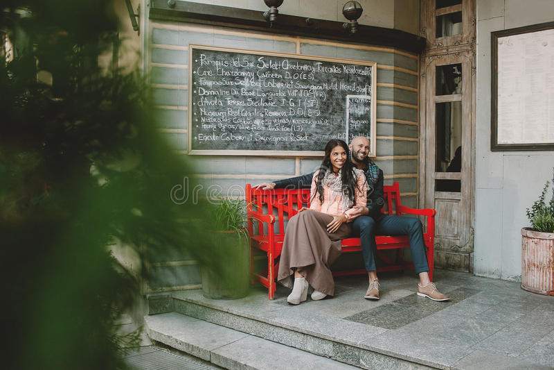 Barnet kopplar ihop sammanträde på den röda bänken nära kafét i staden arkivbild