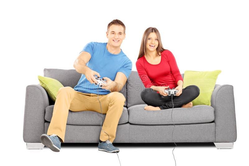 Barnet kopplar ihop sammanträde på en modern soffa och spelavideospel arkivfoton