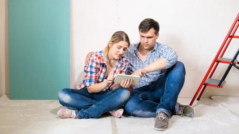 Barnet kopplar ihop sammanträde på golv i hem under construstion och att använda den digitala minnestavladatoren arkivfoton