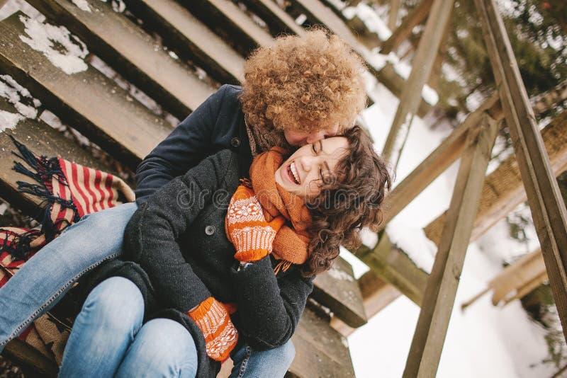 Barnet kopplar ihop sammanträde på trätrappa utomhus i vinter royaltyfri foto