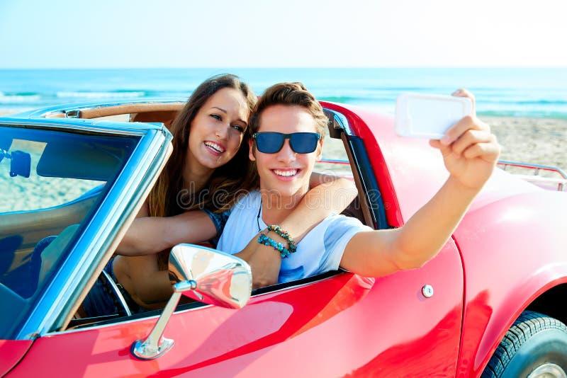 Barnet kopplar ihop selfie som är lycklig i res-bil på stranden arkivbild