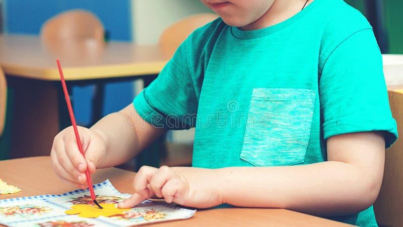 Barnet kopplas in i kreativitet i klassrum Ungekonstverkarbetsplats Barn` s Art Project, hantverk för ungar idérik unge hantverk royaltyfri bild