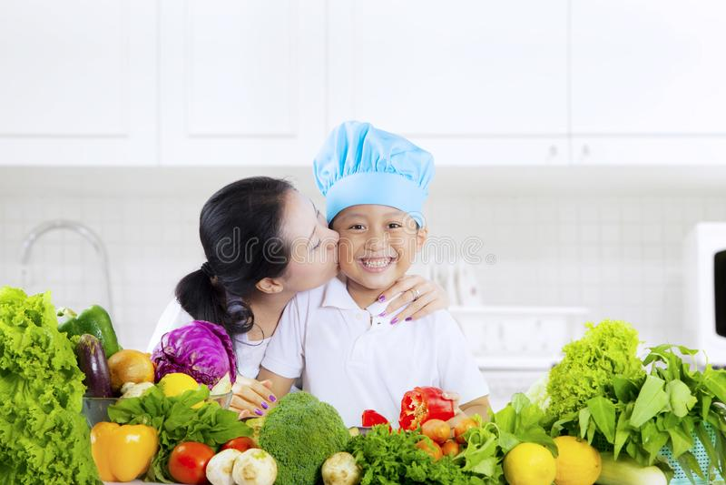 Barnet kysste vid modern med grönsaker i kök fotografering för bildbyråer