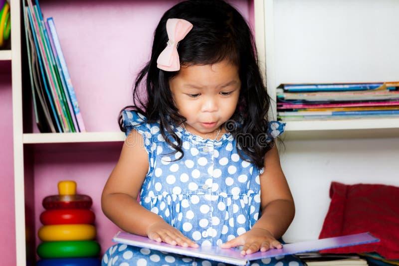 Barnet läste, den gulliga lilla flickan som läser en bok arkivfoton