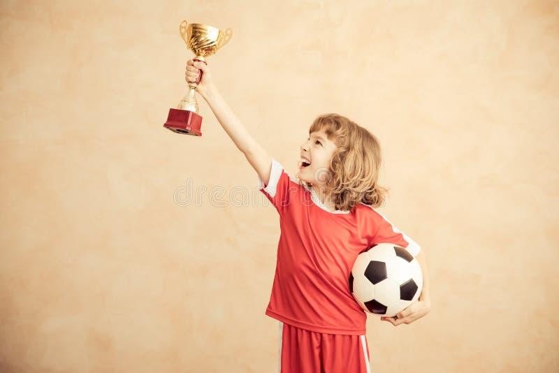 Barnet låtsar för att vara en fotbollspelare royaltyfri fotografi