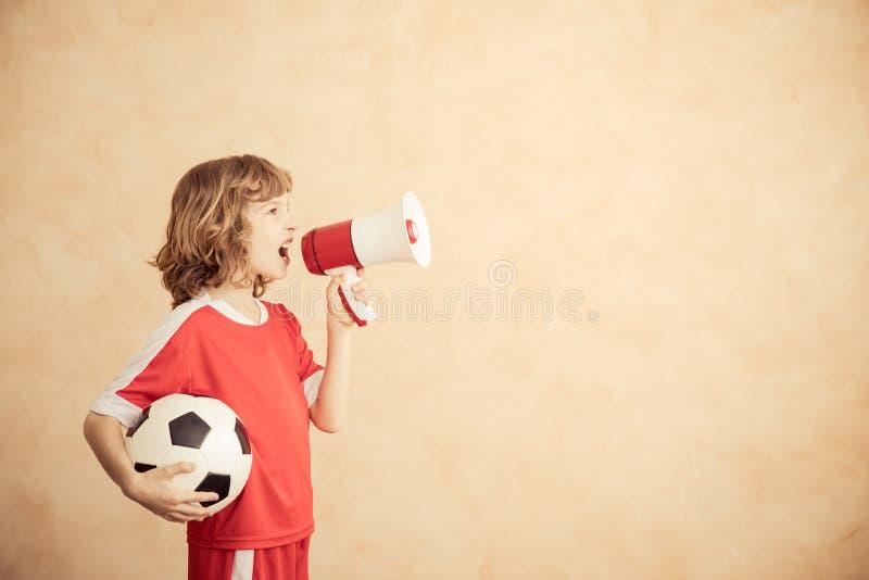 Barnet låtsar för att vara en fotbollspelare royaltyfri foto