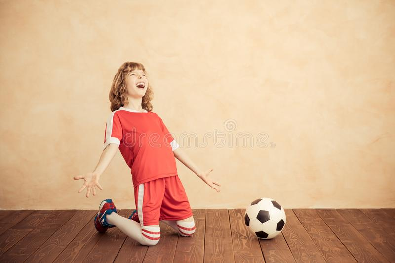 Barnet låtsar för att vara en fotbollspelare fotografering för bildbyråer