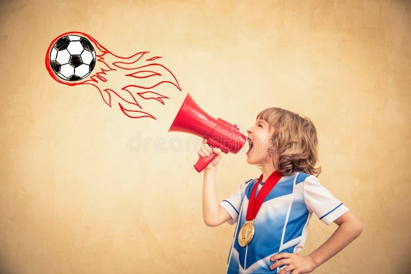 Barnet låtsar för att vara en fotbollspelare royaltyfria foton