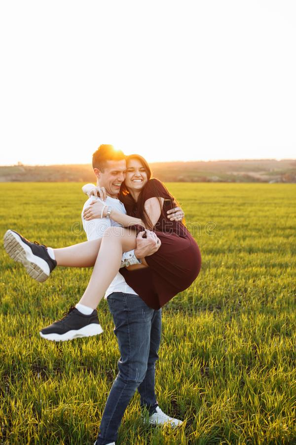 Barnet lyckligt som älskar par, man utomhus att rymma en flicka i hans armar, och att tycka sig om, annonsering och att sätta in  arkivfoton