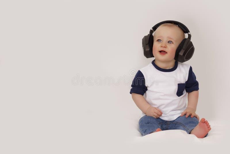 Barnet lyssnar till musik i stor hörlurar fotografering för bildbyråer