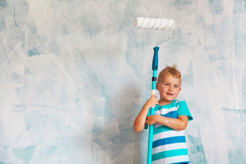 Barnet målar den blåa väggen med en rulle Pojken rymmer en la royaltyfri bild