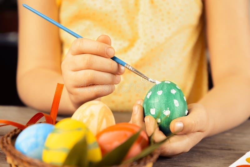 Barnet målar det härliga ägget för påsk arkivfoto