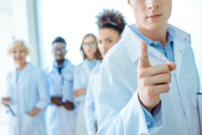 Barnet manipulerar i labblaget som pekar hans finger med gruppen av unga doktorer, i att stå för labblag royaltyfria bilder