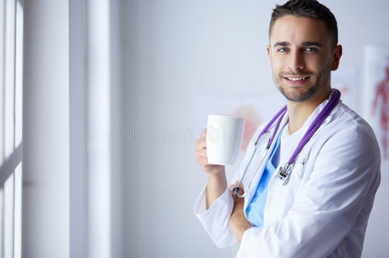Barnet manipulerar med kaffekoppen i medicinskt kontor royaltyfria foton