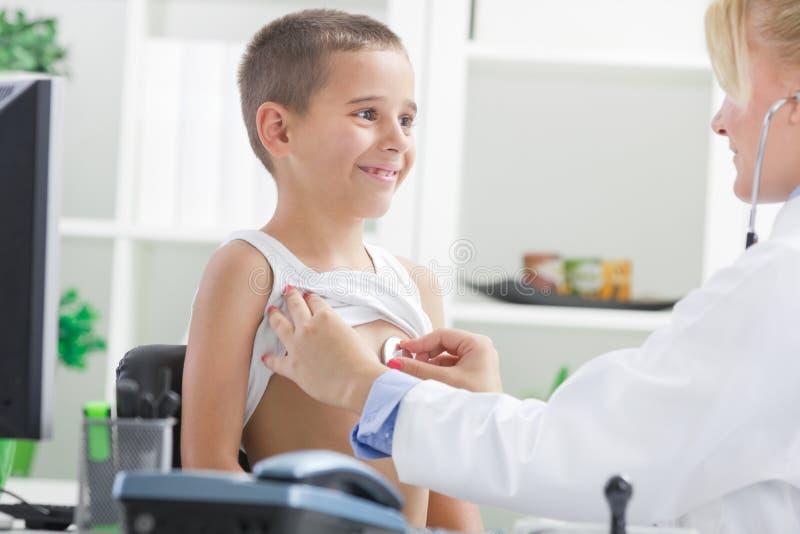 Barnet manipulerar undersöker pojkens baksida med stetoskopet arkivbilder