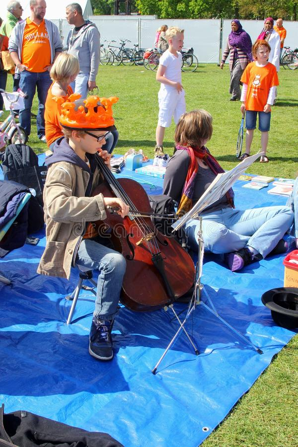 Barnet med den orange kronan spelar en fiol, Holland royaltyfria bilder