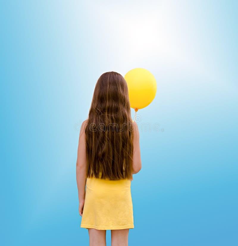 Barnet med en ballong från en baksida arkivfoton