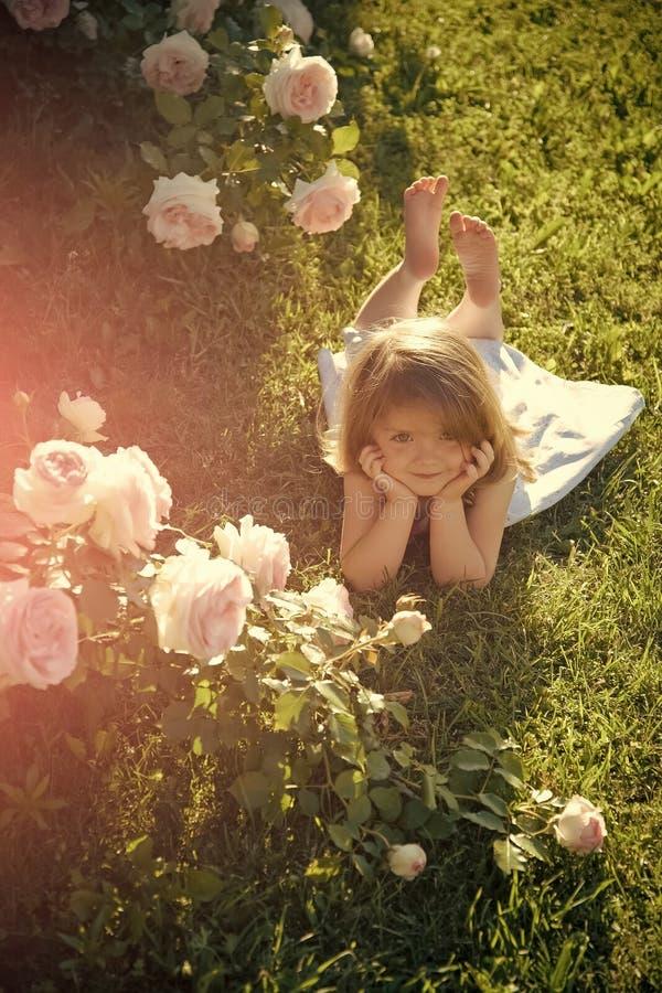 Barnet med gulligt leende på att blomstra steg blommor Tillväxt och blommande Harmlöshet-, renhet- och ungdombegrepp arkivfoto