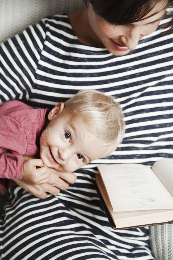 Barnet med modern läser en bok royaltyfria bilder
