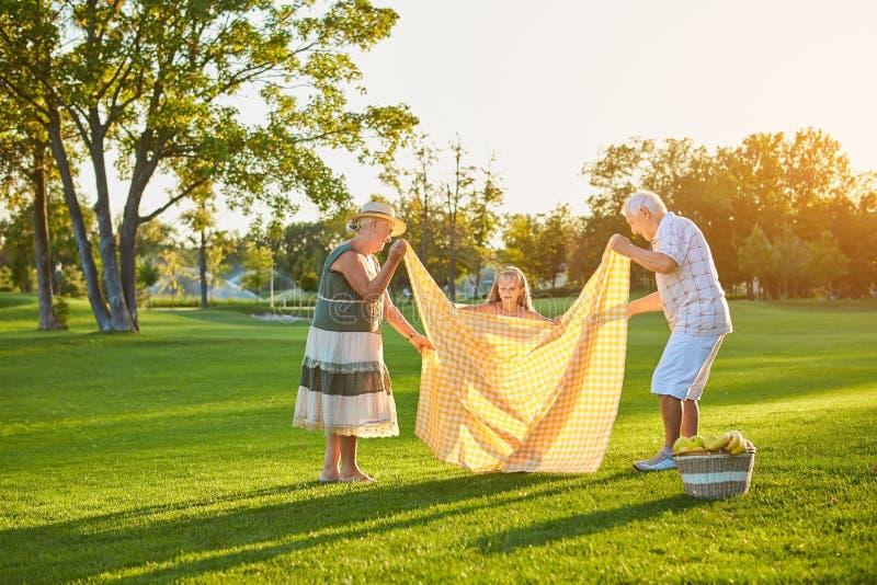 Barnet med morföräldrar, sommar parkerar royaltyfria foton