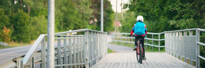 Barnet med ryggs?cken som rider p? cykeln i, parkerar n?ra skola arkivfoto