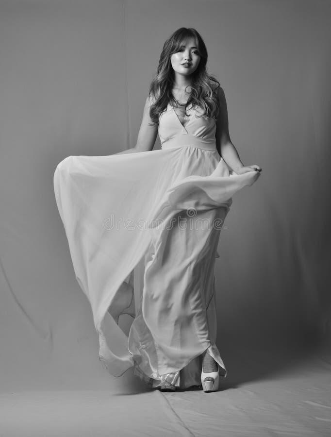 Barnet modellerar att posera i den eleganta långa klänningen som fladdrar i vinden Svart-vit foto royaltyfria foton