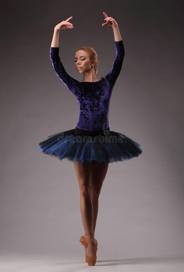 Barnet och den incredibly härliga ballerina i blåttdräkt är posera och dansa i studio Klassisk balett royaltyfri foto