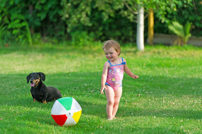 Barnet och hunden spelar i ett gräs royaltyfri bild