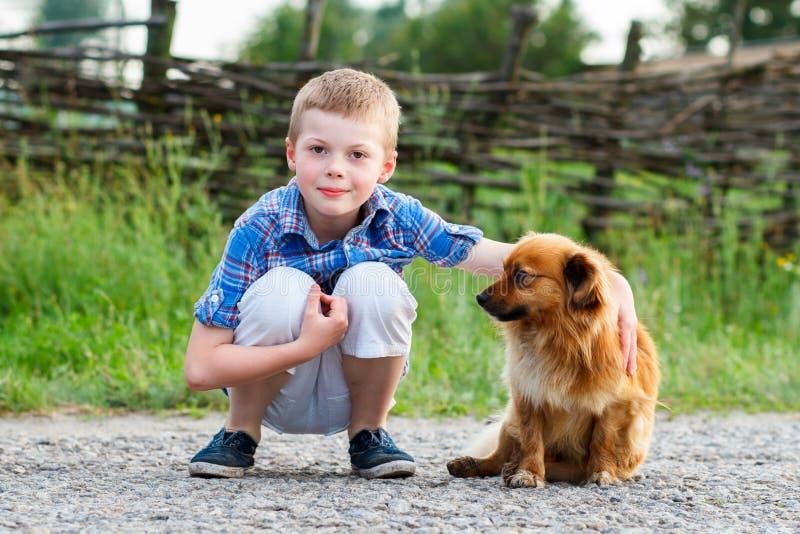 Barnet omfamnar lovingly hans älsklings- hund Bästa vän utomhus- arkivbilder
