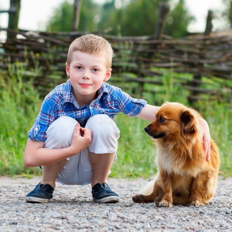 Barnet omfamnar lovingly hans älsklings- hund Bästa vän utomhus- royaltyfria bilder