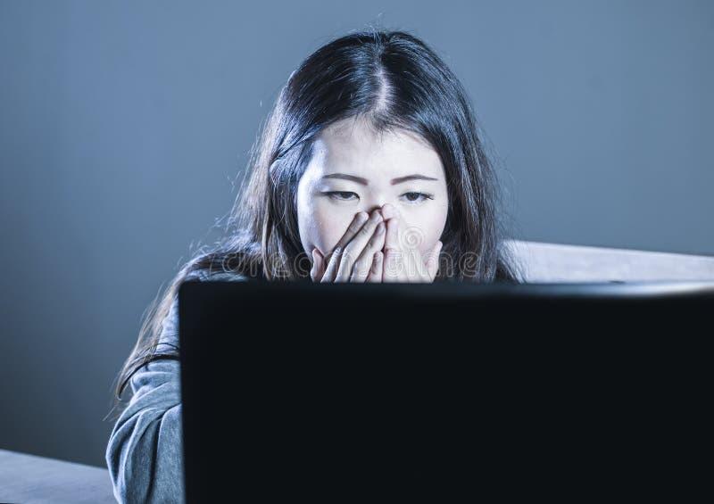 Barnet oroade den asiatiska koreanska studentflickan som ser deprimerat och desperat studera med bärbar datordatoren i spänningen arkivbild