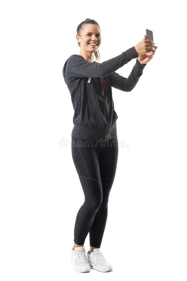 Barnet passade den hållande mobiltelefonen för den idrotts- sportiga kvinnan som skrattar och ser kameran arkivfoto