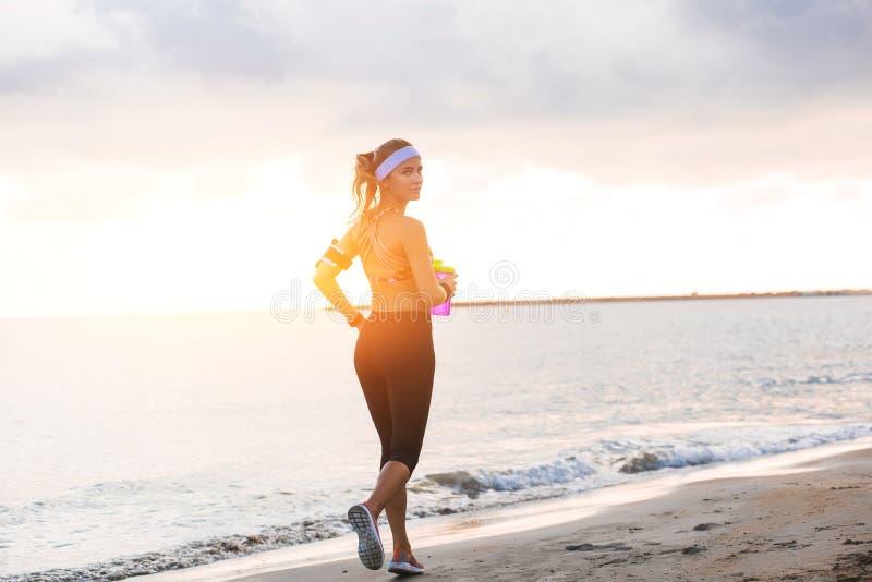 Barnet passade flickan som sträcker på stranden på soluppgång royaltyfria bilder