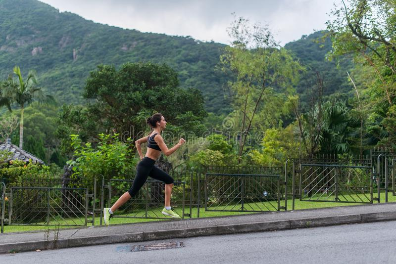 Barnet passade kvinnan som gör den cardio övningen som lyssnar till musik, rinnande det fria med grönt berglandskap i arkivbild