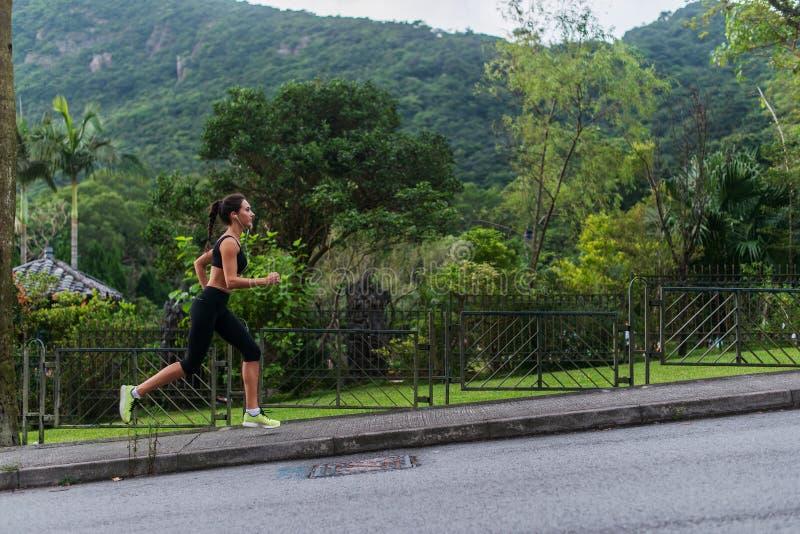 Barnet passade kvinnan som gör den cardio övningen som lyssnar till musik, rinnande det fria med grönt berglandskap i arkivfoton