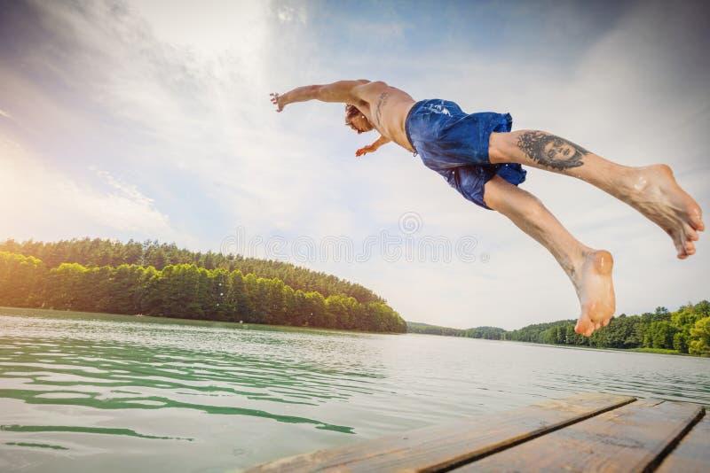 Barnet passade manbanhoppning in i en sjö royaltyfria bilder
