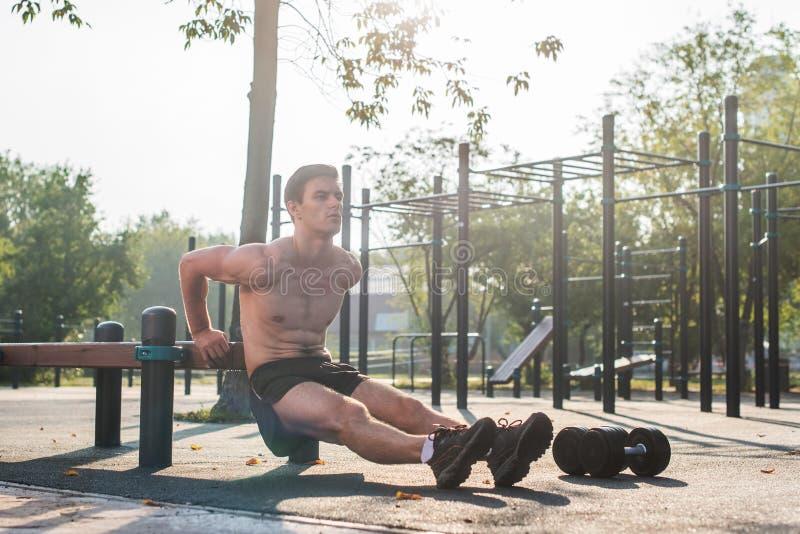 Barnet passade mannen som gör tricepsdoppövningar under utomhus- genomkörare för arg utbildning Manlig modell för kondition royaltyfria bilder