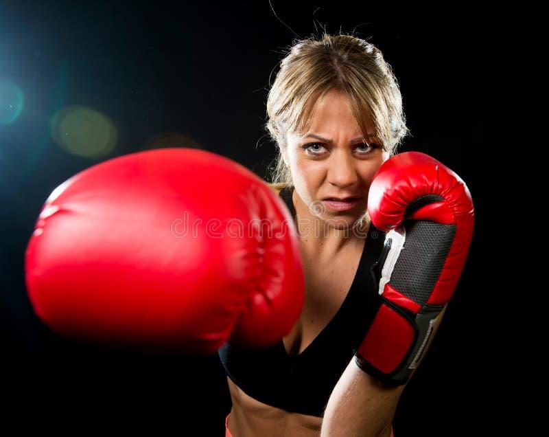 Barnet passade och den starka attraktiva boxareflickan med röda boxninghandskar som slåss kasta aggressiv stansmaskinutbildningsg royaltyfria foton