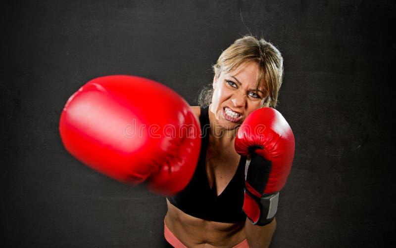 Barnet passade och den starka attraktiva boxareflickan med röda boxninghandskar som slåss kasta aggressiv stansmaskinutbildningsg royaltyfria bilder