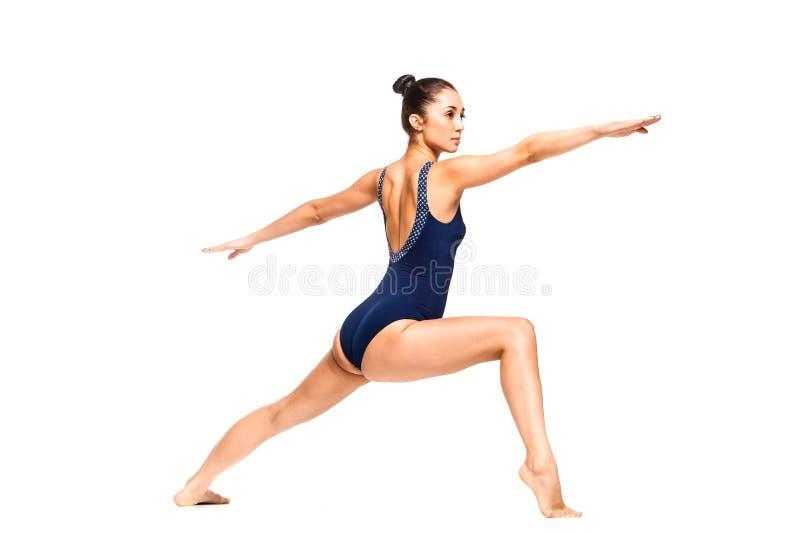 Barnet passade praktiserande yoga för kvinna i krigareposition royaltyfri bild