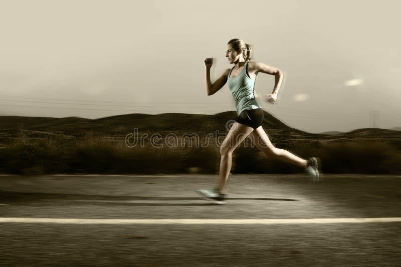 Barnet passade rinnande det fria för sportkvinna på asfaltvägen i berglandskap och den dramatiska ljusuppsättningen för annonseri arkivbild