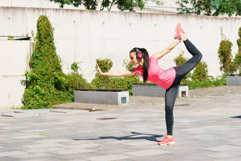 Barnet, passformen och den sportiga kvinnan som gör yoga, övar utomhus- För sport, stads- och sund livsstilbegrepp för kondition, arkivfoton
