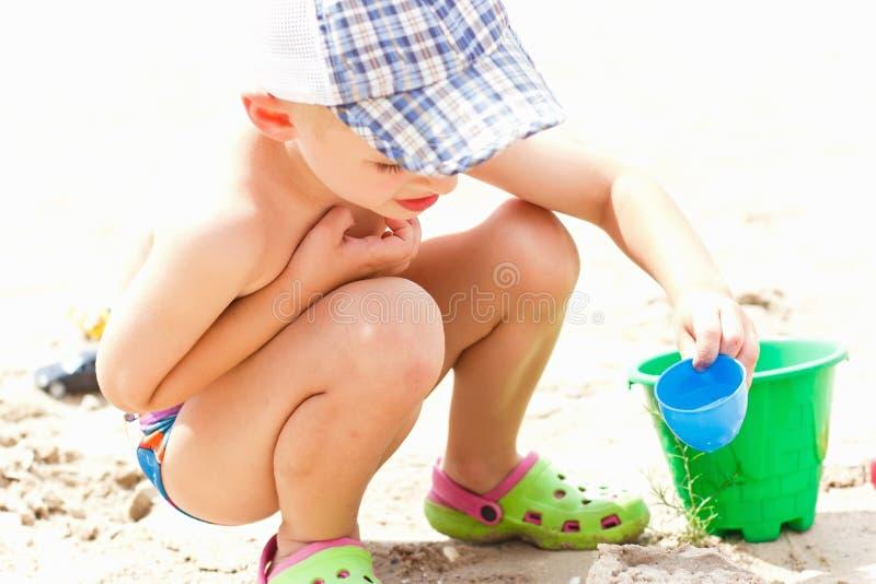 Barnet pojken bygger låset från sand I sommarvacaten royaltyfri bild