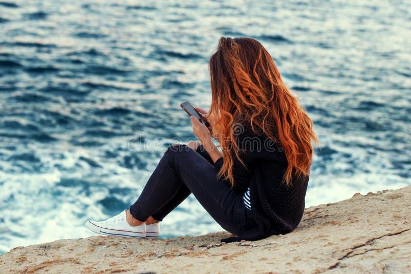 Barnet redhed kvinnan med messaging för lockigt hår på stenig kust på s arkivbilder