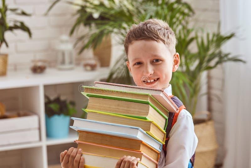 Barnet rymmer en bunt av läroböcker royaltyfri fotografi