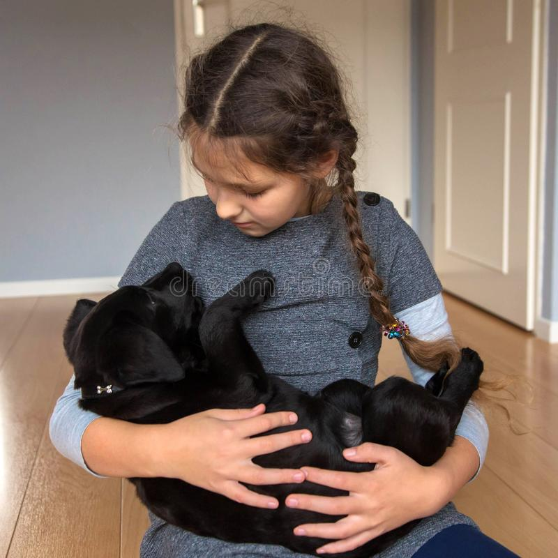 Barnet rymmer en labradorvalp royaltyfria foton