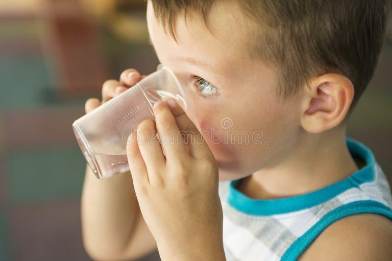 Barnet rymmer en plast- kopp av vatten i hans händer barnet dricker vatten Gullig pys som dricker sötvatten från den plast- koppe royaltyfria bilder